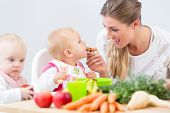 Portrait of a cute and healthy baby girl looking with curiosity at the pink fruit puree, while sitti poster