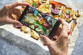 Female Hands Taking Photo Of Food With Mobile Phone. Baked Vegetables On Parchment poster