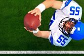 Overhead photo of an American football player wide receiver catching the ball in the air. The unifor