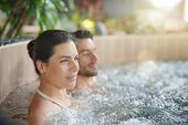 Couple relaxing in spa resort hot pool poster