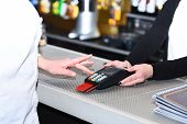 Cashiers Hand Holds Credit Card Terminal On Defocused Background. Customer Enters Pin Code To Pay Wi poster
