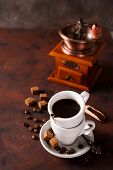Cup Of Steaming Hot Coffee With Coffee Beans, Coffee Grinder, And Coffee Beans Bag On A Stone Brown  poster