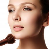 A Young Woman Applied Liquid Foundation On Her Face With A Brush. Beauty Model With Makeup Brush. Br poster