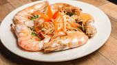 Steamed Seafood Or Steamed Shrimp With Herbs And Vegetable In White Dish On Wood Table. poster