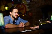 Man With Beard Sits At Bar Counter On Blurred Pub Background. Guy With Serious Face Sitting At Bar C poster