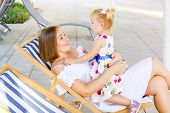 Happy Mother And Daughter Sitting, Relaxing In The Deckchair In The City Park Recreation Area And Ha poster