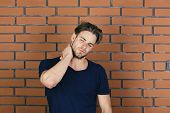 Man With Fair Hair On Red Brick Wall Background. Illnesses And Health Care Concept. Macho With Suffe poster