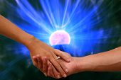 Engagement hands with electronic Plasma Ball. A couple hold hands with a wedding ring against a Plas poster