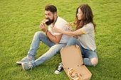 Couple Eating Pizza Relaxing On Green Lawn. Fast Food Delivery. Bearded Man And Woman Enjoy Cheesy P poster