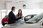 Dealer speaking to a woman in a dealership