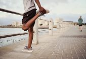 Low Section Of A Male Sportsman Standing Near The Railing Stretching His Leg Before Jogging On The S poster