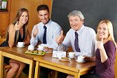 Four happy business people holding their thumbs up in a caf�?�©