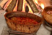 Traditional Way Of Cooking By Open Fire In Clay Pot On Tripod poster