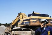 stock photo of jcb  - building engineer with giant bulldozer in background - JPG