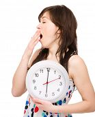 Young woman is holding big clock while yawning, isolated over white