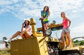young attractive women on old big tractor