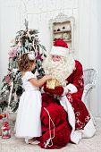 foto of saint-nicolas  - Saint Nicolas gives Christmas gifts to the little girl - JPG