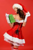 Attractive young woman in Santa Claus costume reading a list of good boys and girls. Red background.
