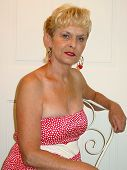 picture of poka dot  - lady with short blonde hair sitting in a chair posing - JPG