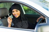 happy arabian woman holding car key inside new vehicle