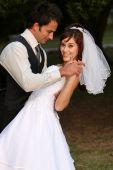 stock photo of wedding couple  - Beautiful wedding couple dancing on the lawn - JPG