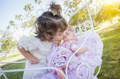 foto of baby doll  - Adorable Young Baby Girl Playing with Her Baby Doll and Carriage Outdoors - JPG