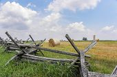 stock photo of split rail fence  - Split rail fence in a lline to left offsets rolled hay bales. ** Note: Visible grain at 100%, best at smaller sizes - JPG