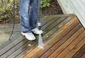 stock photo of pressure-wash  - Man using power washer to clean dirt off of cedar deck - JPG