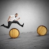 pic of barrel racing  - Concept of difficulty with businessman that jumps obstacles - JPG
