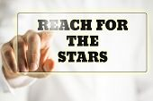 image of reach the stars  - Phrase Reach for the stars on a virtual interface in a navigation bar with male finger touching it from behind - JPG
