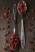 picture of barberry  - Spice barberry in spoons on wooden background - JPG