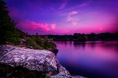 foto of violets  - A violet sunset over a calm lake with trees on a rocky shoreline - JPG