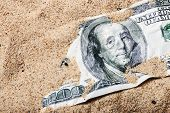 stock photo of sand dollar  - 100 dollar bill buried in the sand - JPG