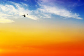 foto of float-plane  - The silhouette of a float or pontoon plane flies off into the sunset - JPG