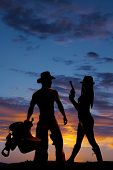 stock photo of western saddle  - a silhouette of a woman holding on to her pistol standing by her cowboy who is holding on to a saddle - JPG
