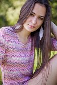 picture of tunic  - Pretty woman with pink tunic in the park sitting on grass - JPG