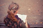 stock photo of sitting a bench  - A young woman is sitting on a park bench in the autumn and is reading a book - JPG