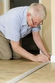 stock photo of baseboard  - A senior adult man measuring new quarter round to replace the old on his baseboards - JPG