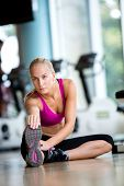 image of stretch  - Cute young woman stretching and warming up for her training at a gym - JPG