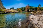 picture of crystal clear  - Fall Foliage On A Crystal Clear Creek In The Hill Country Of Texas, with Deep Blue Skies.