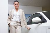 pic of showrooms  - Smiling businesswoman holding a car door handles at new car showroom - JPG