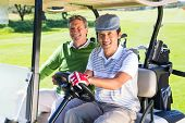 pic of buggy  - Golfing friends driving in their golf buggy smiling at camera at the golf course - JPG