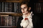 stock photo of dracula  - Handsome vampire nobleman studying ancient books in the library - JPG