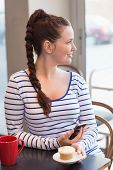 stock photo of have sweet dreams  - Young woman having a cupcake at the cafe - JPG