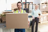 picture of warehouse  - Smiling warehouse worker carrying box in warehouse - JPG