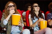 stock photo of cinema auditorium  - Young friends watching a 3d film at the cinema - JPG