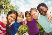 picture of huddle  - Portrait of happy children forming huddle at the park - JPG