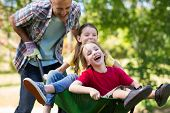 picture of wheelbarrow  - Happy father and his children playing with a wheelbarrow on a sunny day - JPG
