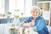 image of smoothies  - Happy senior female with glass of fruit smoothie looking at camera - JPG
