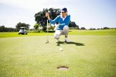 image of ball cap  - Female golfer putting her ball on a sunny day at the golf course - JPG